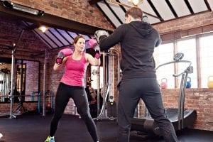 image of a personal trainer boxing with client