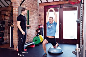 This image shows a personal trainer and his trainee
