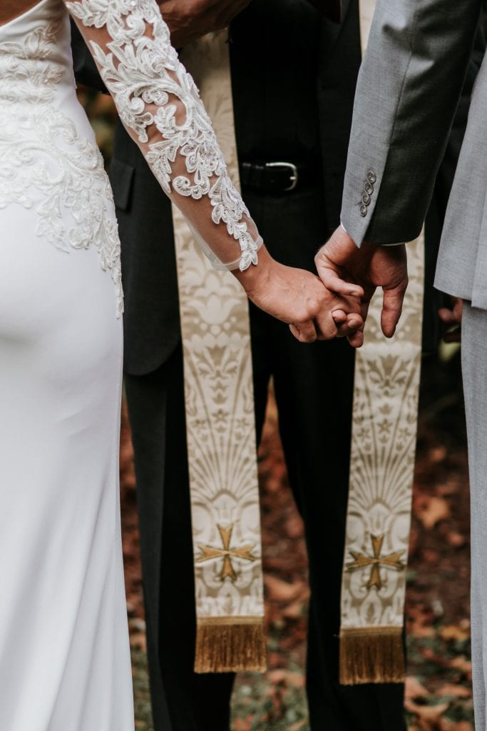 Photo of  a bride and groom holding hands