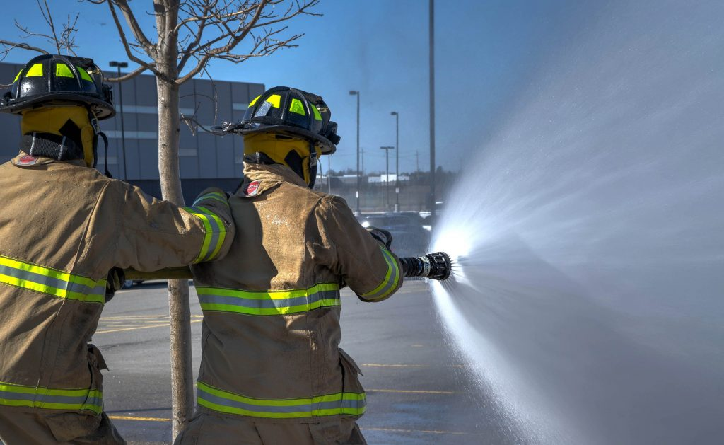 Two fireman holding a hose