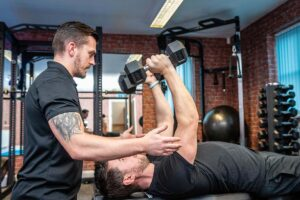 Photo of a client being shown correct form whilst using dumbells inside Elysium Tarporley Gym