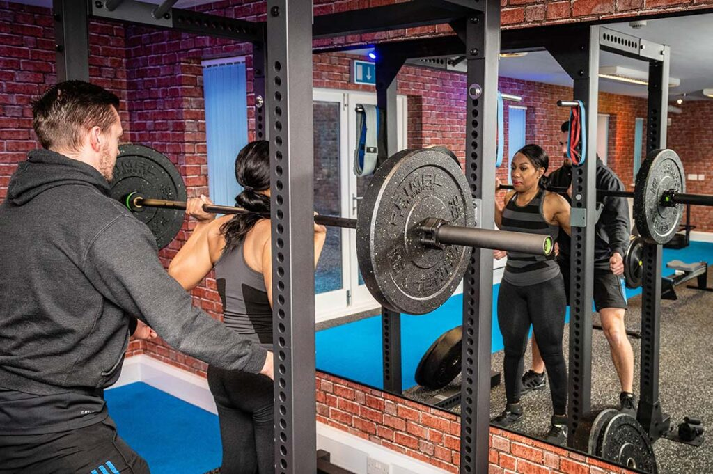 Photo of inside Elysium Tarporley Gym, a client being shown correct form whilst squatting