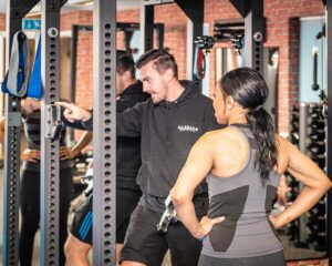 A PT giving directons to a client inside Elysium Tarporley Gym