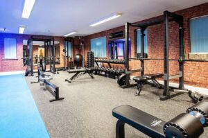 Photo of inside Elysium Tarporley Gym showing the equipemtn, rowing machine, squat rack and benches
